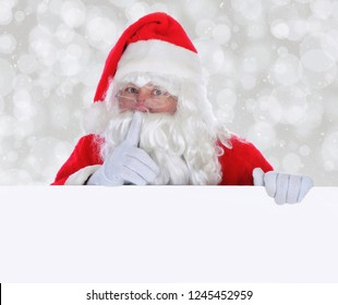 Santa Claus with Blank Sign making shh sign with finger in front of face against a silver bokeh background.