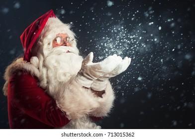 Santa Claus blowing magic snow of his hands