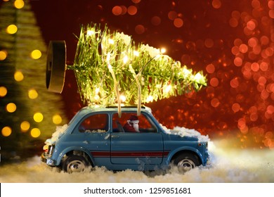 Santa Claus in blue retro toy car delivering Christmas or New Year illuminated tree on festive background