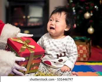 Santa claus bring a gift box to a crying baby girl