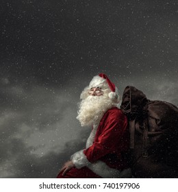 Santa Claus bringing gifts on Christmas Eve: he is sitting on a roof at night, carrying his sack and looking away at the snow falling