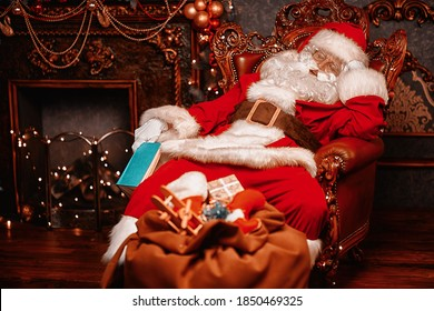 Santa Claus brought gifts for Christmas and fell asleep by the fireplace. Christmas and New Year concept. Home decoration.
