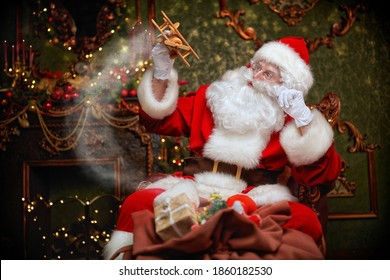 Santa Claus brought gifts for Christmas. He sits in an armchair in a beautiful Christmas interior and plays with a wooden airplane. Christmas and New Year concept.