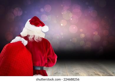 Santa claus carrying sack against shimmering light design over boards
