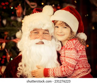 Santa Claus and child at home against Christmas tree. Family holiday concept