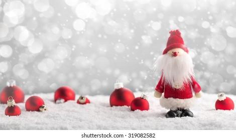 Santa Claus and Christmas balls on snow.