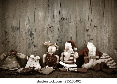 Santa Claus Christmas card wooden background with a space for text and old rag dolls Christmas decorations