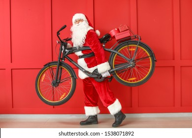 Santa Claus with Christmas gifts and bicycle on color background