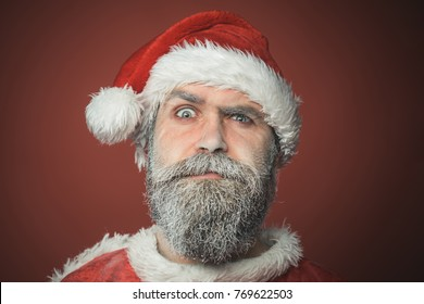 Santa Claus, Christmas, New year, holiday, winter. Surprised bearded man in Santa Claus hat on red background. Merry Christmas and Happy New Year!