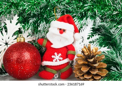 Santa Claus with Christmas red ball, bump and white snowflakes on a background of green garland