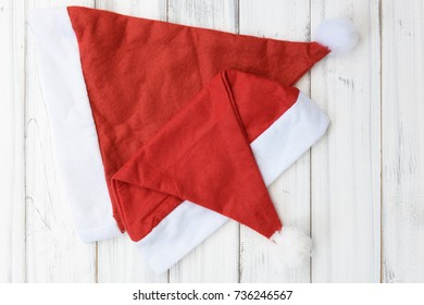 Santa Claus Christmas red hat on white wooden background,flat lay