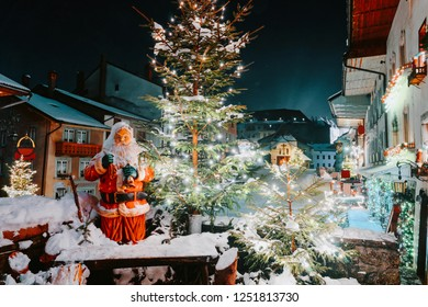 Santa Claus and Christmas tree in Gruyeres town village in Switzerland in winter at night.
