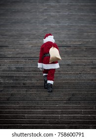 Santa claus climbing stairs. Present delivery concept .