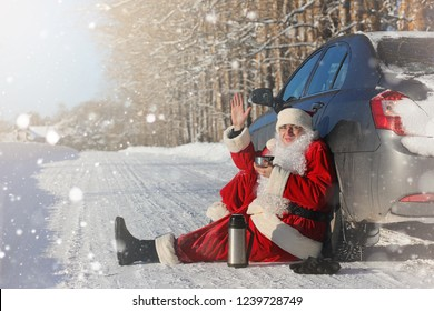 Santa Claus comes with gifts from the outside. Santa in a red suit with a beard and wearing glasses is walking along the road to Christmas. Father Christmas brings gifts to children.
