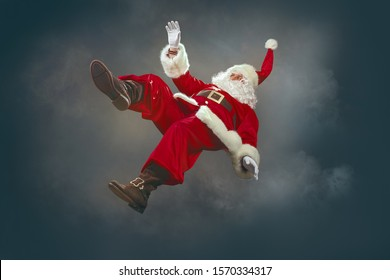 Santa Claus is coming down from the sky. The levitation of Santa Claus doing magic at night.