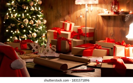 Santa Claus costume and hat hanging on chair at table with Merry Christmas wish list decor gifts presents on holiday eve in cozy Santa home workshop interior late in night with light on xmas tree.