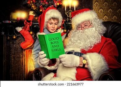 Santa Claus and a cute boy reading a list of good boys and girls. Christmas home d�©cor.