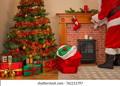 Santa Claus delivering gift wrapped presents under the tree on Christmas Eve with a sack full of toys for good girls and boys.