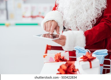 Santa Claus doing Christmas shopping at the supermarket, he is using apps on a digital tablet and pushing a cart filled with gift boxes