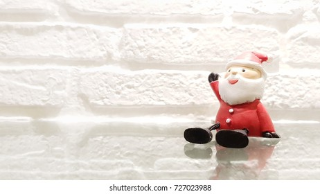 santa claus doll on grass and white brick wall. Marry x-mass and happy new year 2018