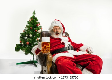 Santa Claus drinking beer near the Christmas tree, congratulating, looks drunk and happy. Caucasian male model in traditional costume. New Year 2020, gifts, holidays, winter mood. Copyspace for your