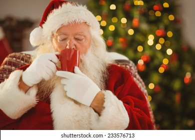 Santa claus drinking a hot beverage at home in the living room