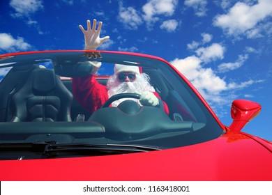 Santa Claus. Santa Drives fast in his Red Sports Car with a Blue Sky and fluffy white clouds. Santa Hot Rod. Santa Claus sleigh.
