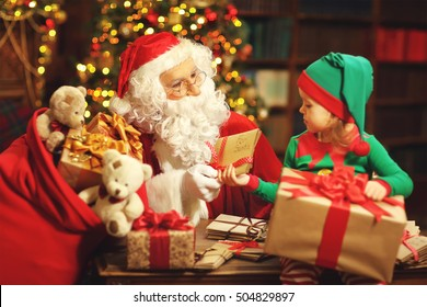 Santa Claus and a elf child in a Christmas working, reading letters and prepare gifts