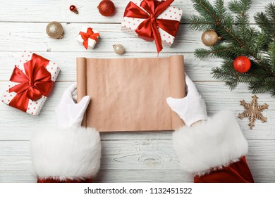 Santa Claus with empty wish list at table, top view. Christmas celebration