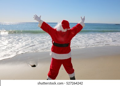 Santa Claus enjoys a Day at the Beach. Santa loves the ocean. Santa Claus in the sand. Christmas vacation.