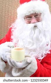 Santa Claus Enjoys his glass of Eggnog. Santa Claus drinks Eggnog for Christmas. Eggnog Drink. Holiday Traditional beverage. Food and Beverage,