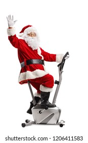 Santa Claus exercising on a stationary bicycle and waving isolated on white background