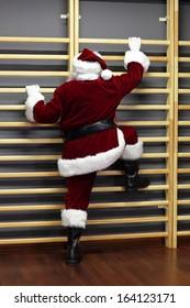 santa claus exercising with wall bars,Christmas Time preparation