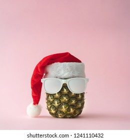 Santa Claus face made with pineapple and white painted sunglasses. Christmas concept.
