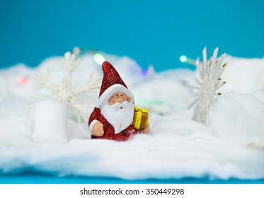 Santa Claus figurine with gift on blue background