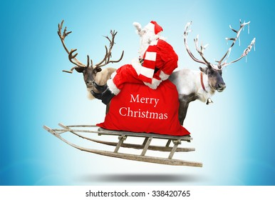 Santa Claus flies in a sleigh with reindeer - Shutterstock ID 338420765