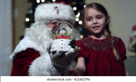 Santa Claus in front of a christmas tree in living room