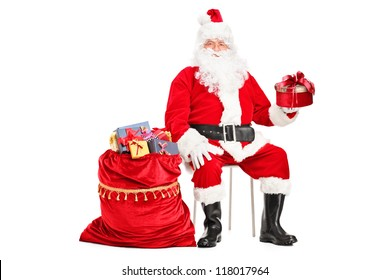 Santa Claus with a gift sitting next to a bag full of presents isolated on white background