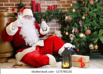 Santa Claus with gifts sitting next to a Christmas tree