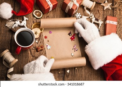 Santa Claus with gifts and wish list on wooden table