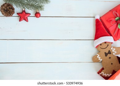 Santa claus gingerbread man cookie inside open gift box and fir branch decoration on vintage wooden table background, flat lay with copy space