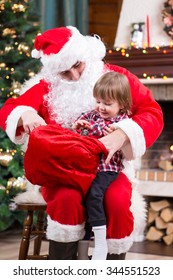 Santa Claus giving a present to kid boy near the fireplace and Christmas tree at home