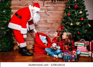 Santa Claus giving a present to a little cute girls near Christmas tree at home