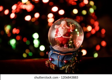 Santa Claus in a glass snowglobe under the tree at the new year time