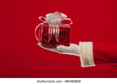 Santa Claus gloved hand with giftbox, on a red background