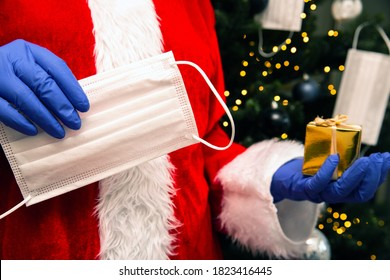 Santa Claus with gloves and face mask for Coronavirus by the Christmas tree, holding a golden present, Covid-19 and Christmas safety concept closeup