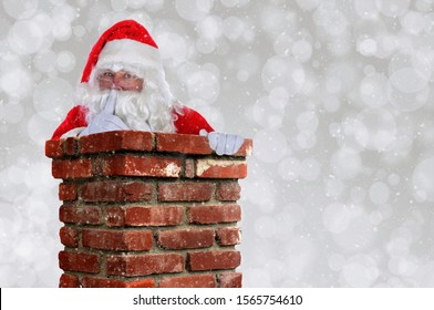 Santa Claus Going Down Chimney making Shh sign with finger to lips. Horizontal with silver bokeh background and snow effect and copy space.