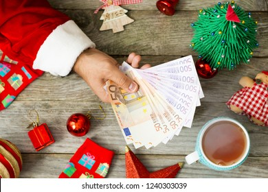 Santa Claus hand giving euro banknotes against Christmas background