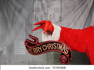 Santa Claus Hand or Grinch Hand holds a Merry Christmas Sign.