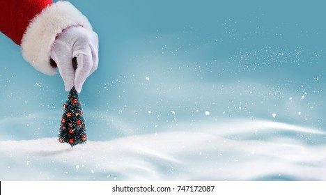 A santa claus hand hold a christmas tree.Christmas winter scene